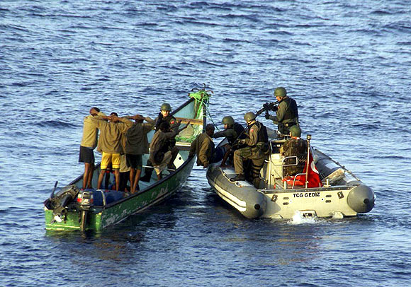 Marines from NATO's Turkish frigate Gediz arrest suspected pirates on their skiff in the Gulf of Aden September 26, 2009