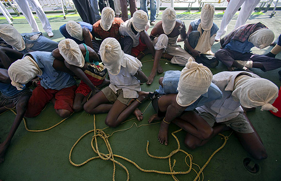 Suspected Somali pirates sit with their faces covered with cloth sacks on the deck of an Indian Coast Guard vessel in Mumbai