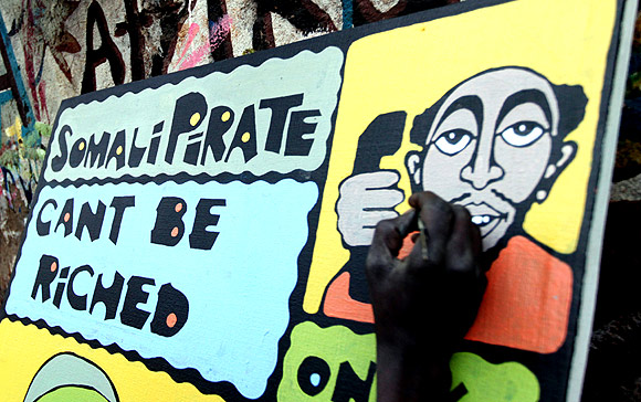 A Kenyan artist paints an anti-pirate graffiti on a wooden board at the sprawling Kibera slums in Kenya's capital Nairobi
