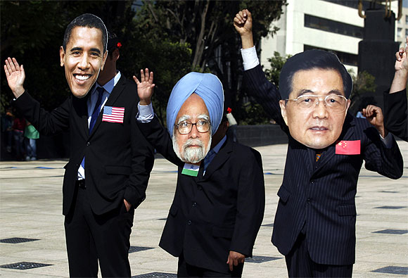 Activists wear masks of G-20 leaders (L-R) U.S. President Barack Obama, Prime Minister Manmohan Singh and Chinese President Hu Jintao