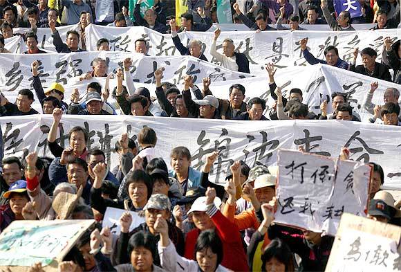 Residents raise their fists as they chant slogans and hold banners during a rally in the village of Wukan in Lufeng county, Guangdong province, China