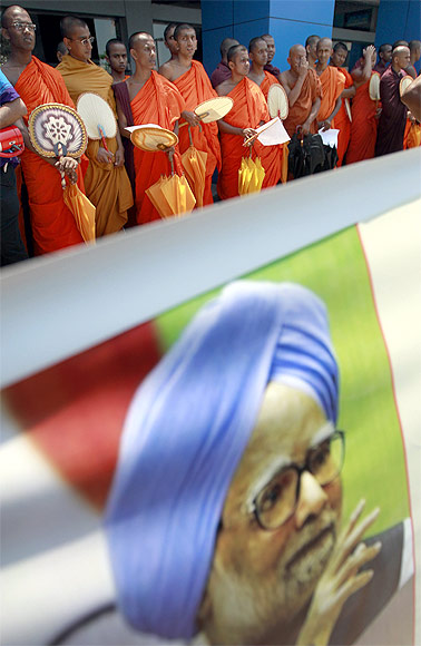 Buddhist monks stand near an image of Dr Singh