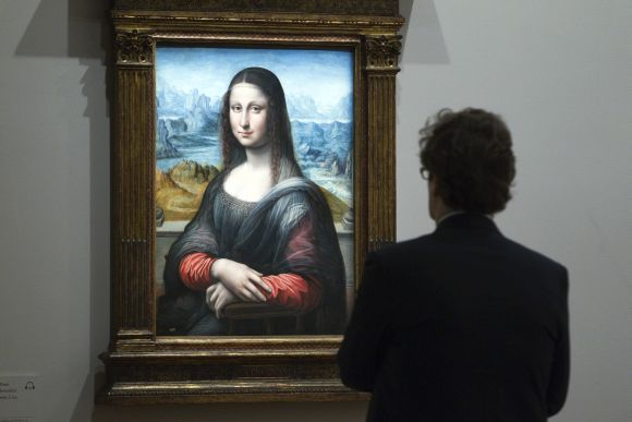 A visitor looks at a copy of Da Vinci's 'Mona Lisa' painting at a museum in Paris