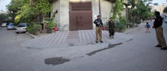 A police officer and private security guard stand outside the residence of Hafiz Saeed
