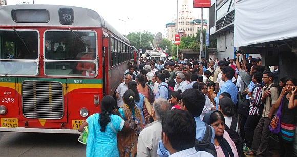 People clamour for space at a bus stand in Mumbai