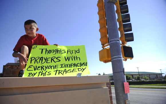Brendon Hutchinson, 11, of Aurora, Colorado sits at the intersection north of the Century 16 theater shootings in Aurora