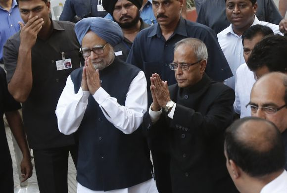 Prime Minister Manmohan Singh and newly elected President Pranab Mukherjee gesture to the media outside the latter's residence in New Delhi on Sunday
