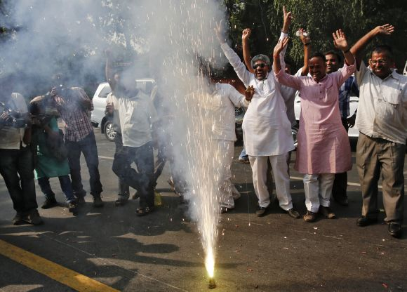Congress supporters let off a firecracker as they celebrate the election of their leader Pranab Mukherjee as India's 13th President, in New Delhi