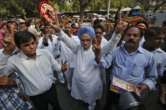 A Congress supporter dressed as PM Manmohan Singh celebrates with other supporters the election of their leader Mukherjee as India's 13th president in New Delhi