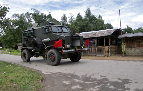 An army bullet-proof vehicle patrols through a street during curfew near Kokorajhar town in Assam