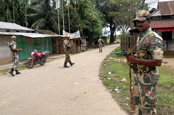 Security personnel patrol on a street during curfew near Kokorajhar town