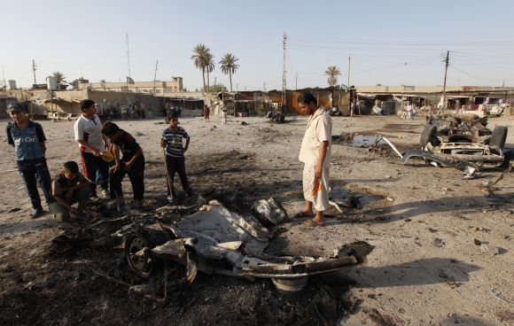 Residents gather at the site of a car bomb attack in Mahmudiya, 30 km south of Baghdad, on Monday.