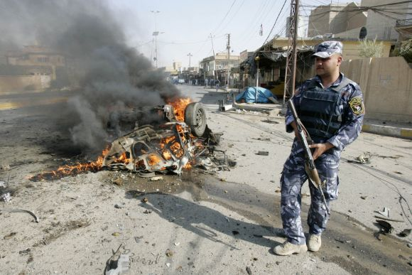 A policeman stands guard at the site of a bomb attack in Kirkuk, on Monday