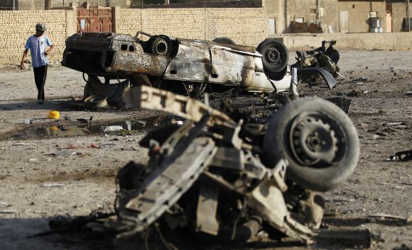 A boy stands near the site of a car bomb attack in Mahmudiya, on Monday