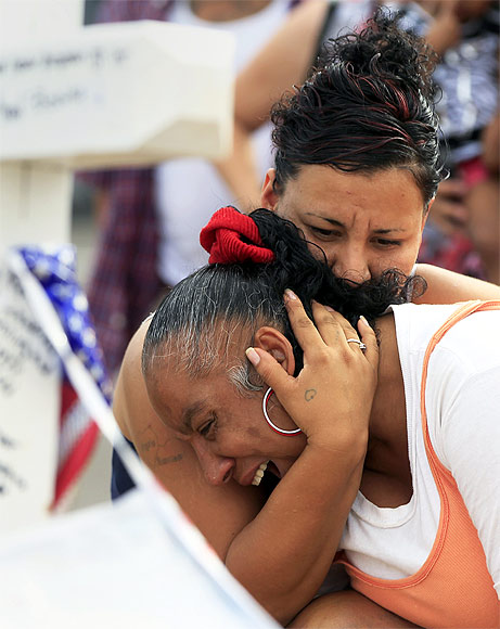 Denise Paba, who lost her 6-year-old niece Veronica Moser, is comforted by a woman as she cries at a memorial for victims behind the theatre where a gunman opened fire last Friday on moviegoers in Aurora
