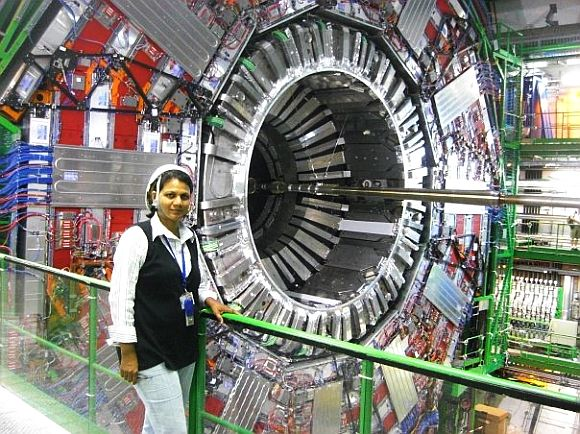 Archana Sharma stands next to the Large Hadron Collider at the CERN facility