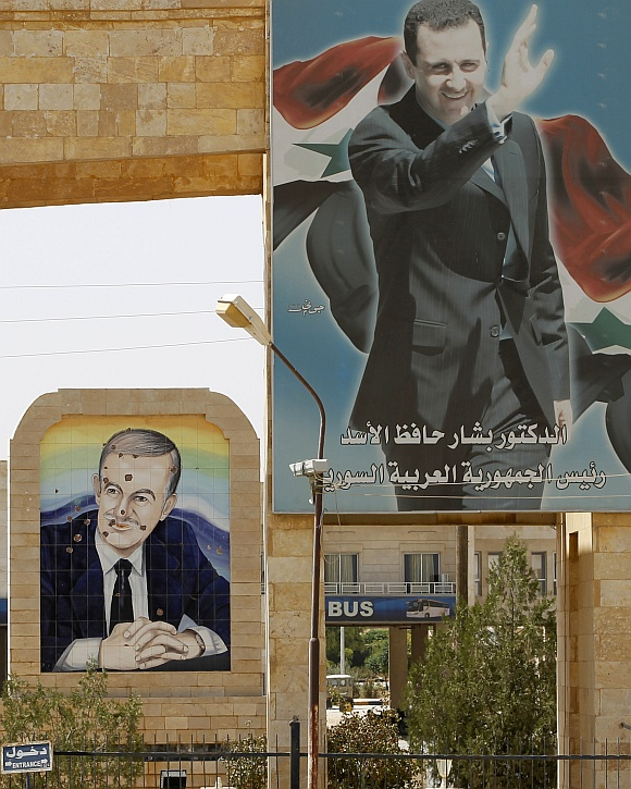 Portraits of Syrian President Bashar al-Assad (top) and his father former Syrian President Hafez al-Assad (rear) are seen at the Rabia border crossing, the main border post between Iraq and Syria