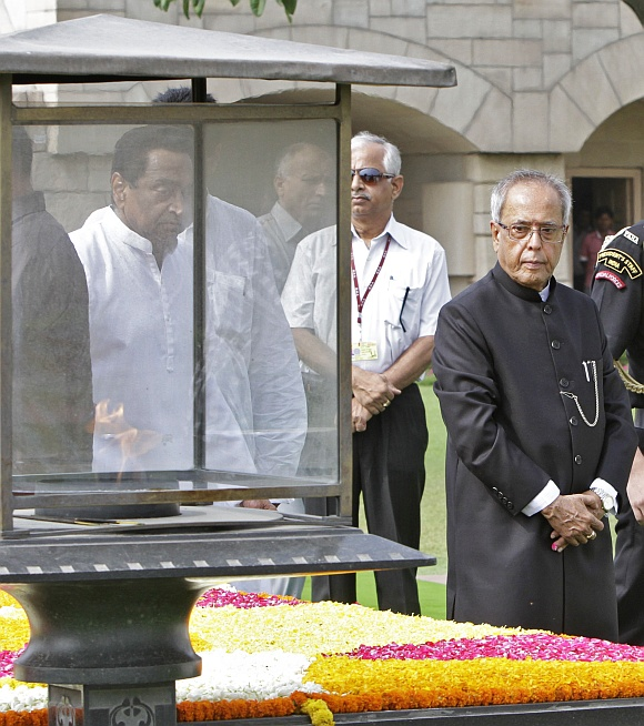 Newly elected President Pranab Mukherjee walks after paying respect at the Mahatma Gandhi memorial at Rajghat in New Delhi