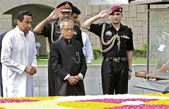 Newly elected President Pranab Mukherjee (C) pays respect at the Mahatma Gandhi memorial at Rajghat in New Delhi