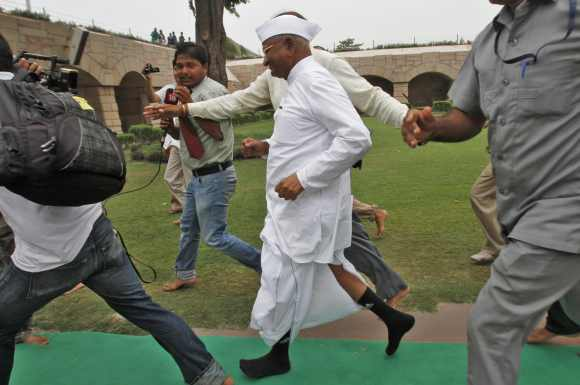 Anna Hazare runs from his supporters after paying respects at the Mahatma Gandhi memorial at Rajghat, ahead of his protest against corruption in New Delhi July 25