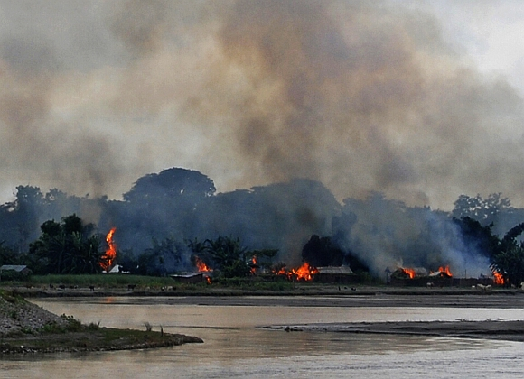 Flames erupt from huts built on the banks of river Gourang during violence near Kokrajhar town in Assam