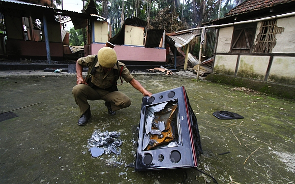 A policeman inspects a damaged television set in the forecourt of a burnt house during violence near Goshaigaon town in Assam