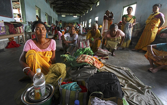 Villagers affected by the ethnic riots sit with their belongings inside a relief camp near Goshaigaon town, in Assam