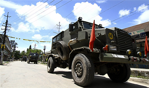 Army vehicles patrol a deserted road during the curfew in Kokrajhar town