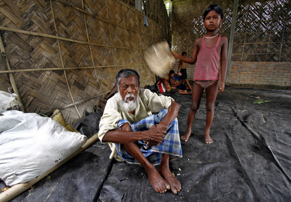 Jahar, a villager affected by the ethnic riots, at a relief camp near Bijni town, as his granddaughter fans him