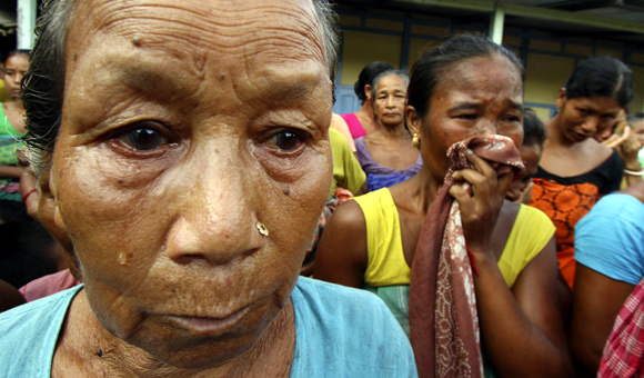Women, whose homes were burnt down, weep at a relief camp in Goshaigaon town