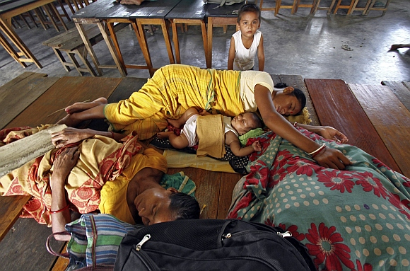 Villagers affected by ethnic riots rest inside a relief camp along with their children at Bijni town in Assam