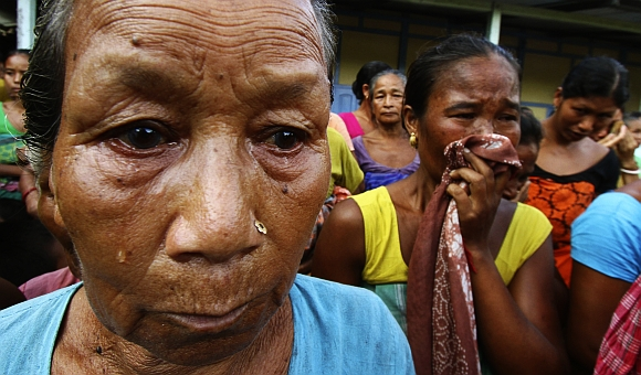 Village women affected by the ethnic riots, cry after their houses were burnt during violence, at a relief camp at Goshaigaon in Assam