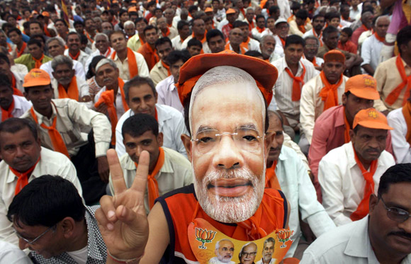 A supporter wears the mask of Narendra Modi during a rally
