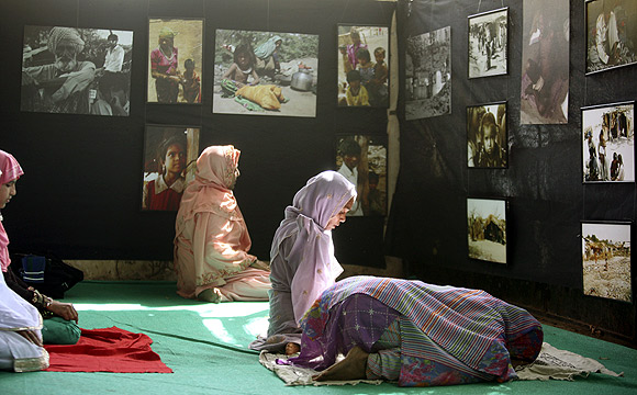 Muslims pray in a hall where a photo exhibition on Gujarat riots is being held