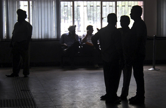 People stand inside the driving registration and license authority office during a power-cut in Chandigarh