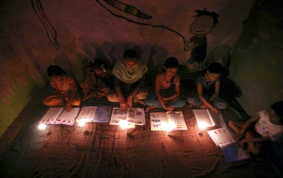 Muslim girls study in the light of candles inside a madrasa or religious school during power-cut in Noida on the outskirts of New Delhi