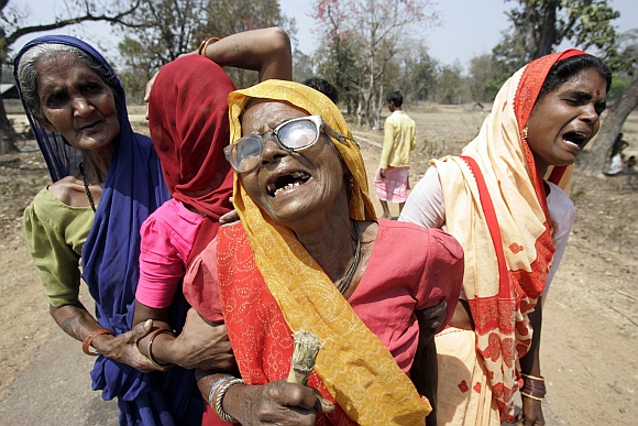Relatives of tribal militias killed in a Maoist attack cry at the cremation in Mangapeta village, about 450 km from Raipur
