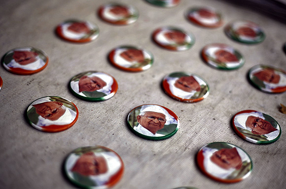Badges with portraits of activist Anna Hazare are displayed for sale