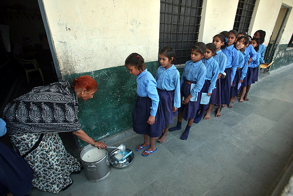Children stand in line to collect their free mid-day meal