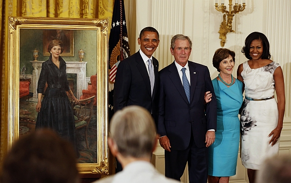 Former US President George W Bush stands next to U.S. President Barack Obama while former first lady Laura Bush stands next to first lady Michelle Obama during the unveiling of their official White House portraits in the East Room of the White House in Washington