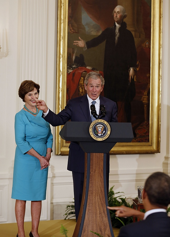 Former US President George W Bush stands next to former first lady Laura Bush while speaking during the unveiling of their official White House portraits in the East Room of the White House in Washington. US President Barack Obama is seen at the lower right corner