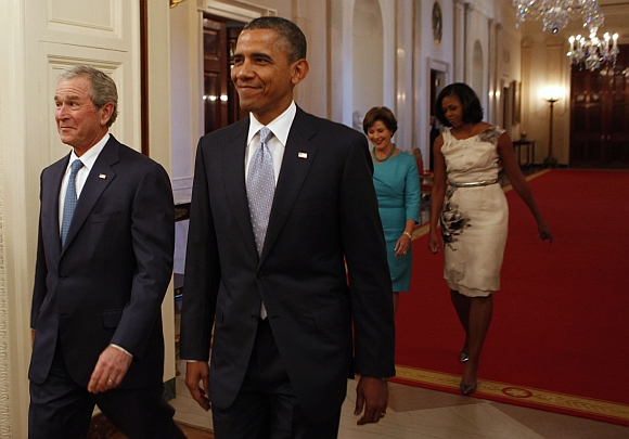 Former US President George W Bush walks next to US President Barack Obama while former first lady Laura Bush walks next to first lady Michelle Obama before the unveiling of the Bushs' official White House portraits in the East Room of the White House in Washington