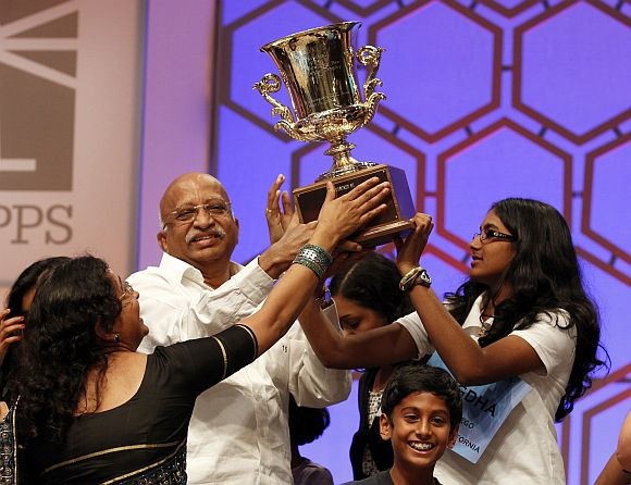 Snigdha Nandipati holds her trophy along with family members after winning the Scripps National Spelling Bee