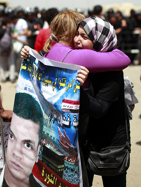 Relatives of people who died during Egypt's revolutions hug each other after the sentencing