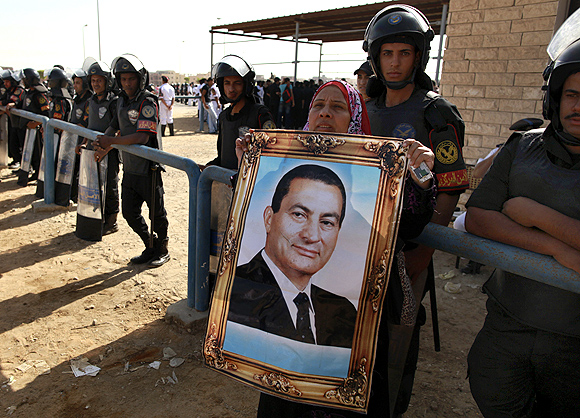 An Egyptian woman holds a picture of former president Hosni Mubarak outside the police academy where he was sentenced to life imprisonment on Saturday
