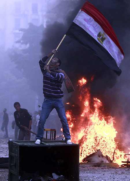 A protester waves an Egyptian flag during clashes with army soldiers at the cabinet near Tahrir Square in Cairo