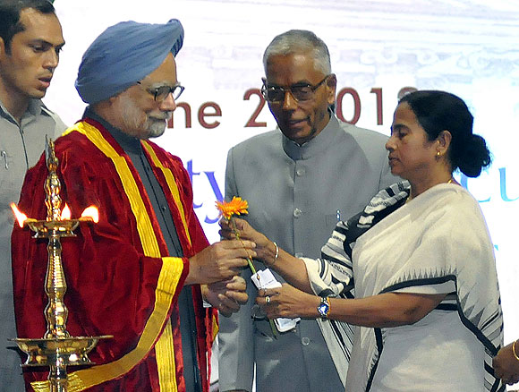 West Bengal Chief Minister gives a flower to Prime Minister Manmohan Singh as Governor M K Narayanan looks on at the Science Congress in Kolkata on Saturday