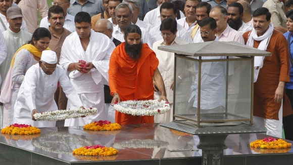 Ramdev and Anna Hazare place wreaths at the Mahatma Gandhi memorial at Rajghat