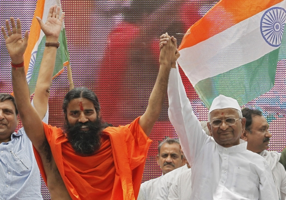 Swami Ramdev and activist Hazare raise their hands during their day-long hunger strike against corruption in New Delhi