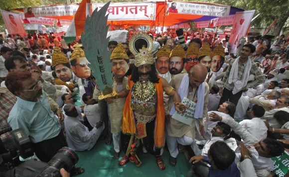 A man, dressed up as the 10-headed mythical demon king Ravana with portraits of Indian politicians, takes part in the day-long hunger strike